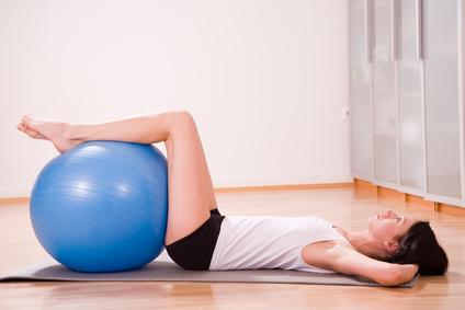 Junge Frau trainiert mit Gymnastikball